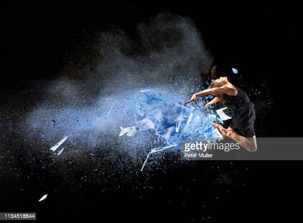 female dancer mid air with blue powder explosion - vitality stock pictures, royalty-free photos & images