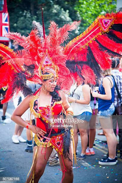 Female dancer with bright feathers dances for the crowd at the Notting Hill Carnival.