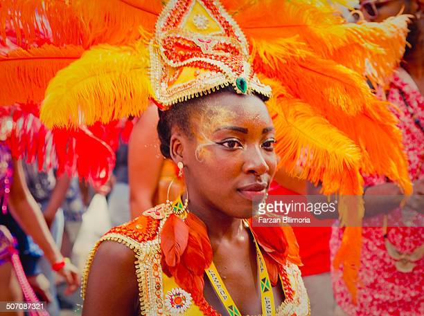 Female dancer with bright orange feathers dances for the crowd at the Notting Hill Carnival.