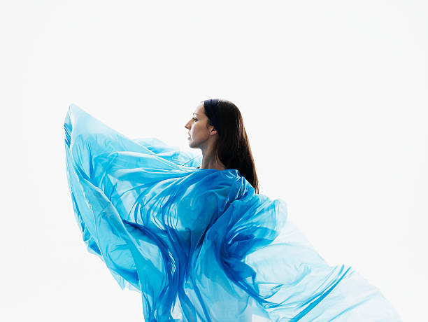 Female dancer wrapped in blue fabric on white background, side view