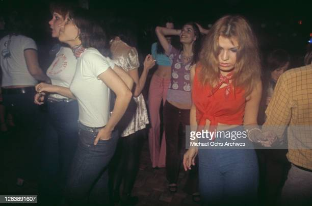 Female dancers in t-shirts, tie-front blouses and jeans on the dancefloor at Rodney Bingenheimer's English Disco, a nightclub on Sunset Boulevard in...