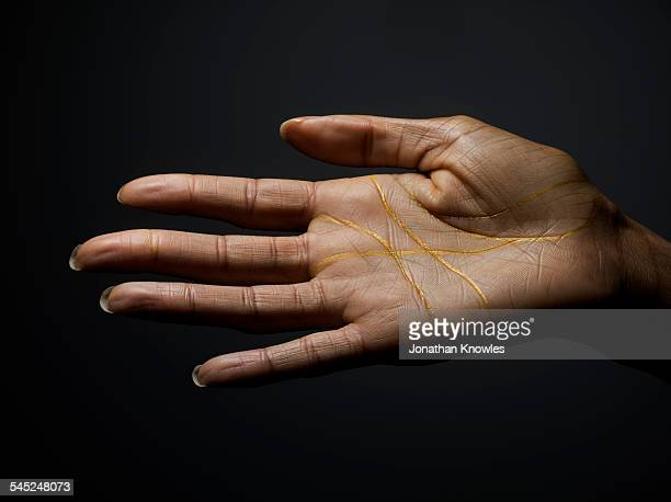 Female dark skinned hand covered with gold lines