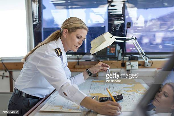 Female deck officer working on a nautical map