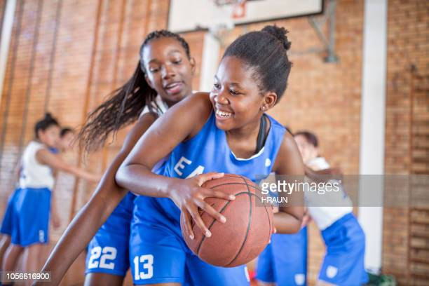 female defending basketball from opponent - basketball sport stock pictures, royalty-free photos & images