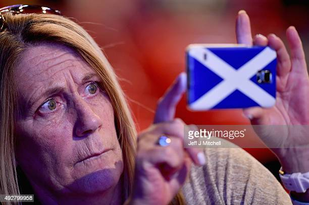 A female delegate takes a photo on her mobile phone as she attends the 81st SNP conference at the Aberdeen Exhibition and Conference centre on...