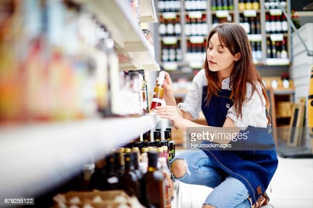 dono de lanchonete feminino organizando garrafa de molho para salada na prateleira na loja - convenience store - fotografias e filmes do acervo