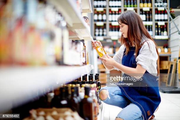 female deli owner examining bottle of salad dressing in store - convenience store stock photos and pictures