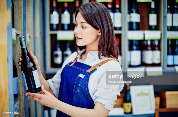 Female deli owner examining wine bottle in store