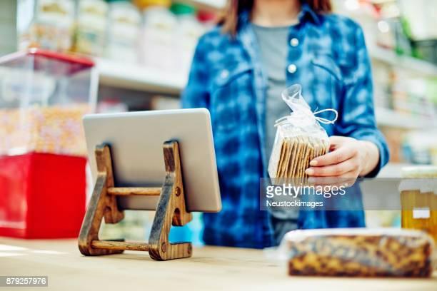 Female deli owner holding cracker package by digital tablet