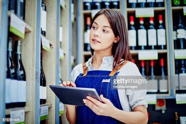 Female deli owner holding digital tablet at alcohol section
