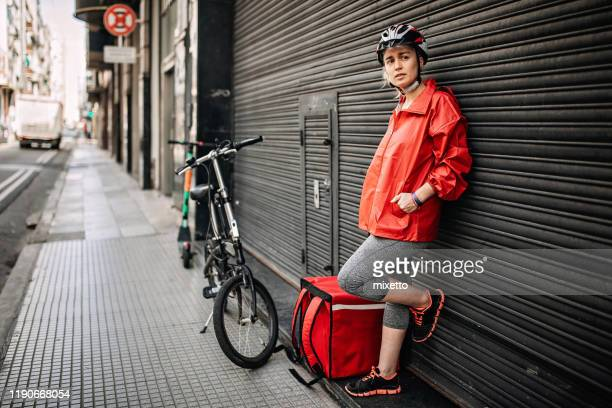 female delivery person in uniform standing on the street - hands in pockets stock pictures, royalty-free photos & images