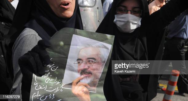 Female demonstrator holds a poster of Mir Hossein Mousavi, the defeated presidential candidate, while on march towards Azadi Square, Tehran, 15th...