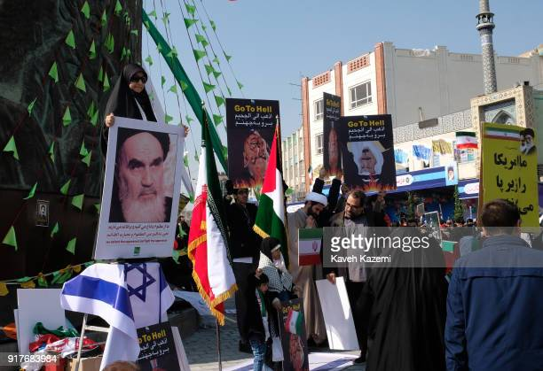 A female demonstrator in black chador holding a banner with photo of Ayatollah Khomeini stands on an Israeli flag on a platform above the ground...