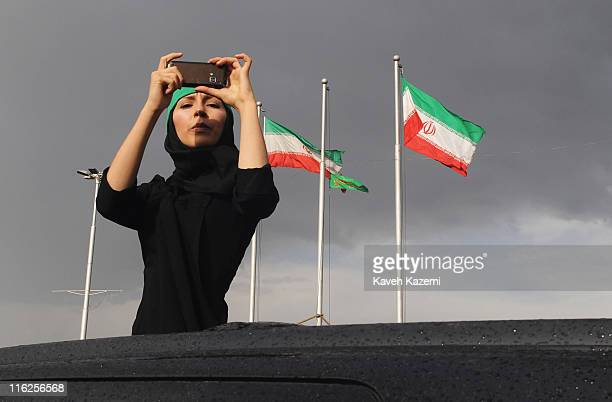 A female demonstrator wearing a green headband takes a souvenir photograph from a car in Azadi Square Tehran 15th June 2009 The headband shows...