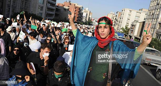 A female demonstrator with green ribbon around her forehead and fingers flashes Vsigns during a peaceful march in Karimkhan Street Tehran 17th June...