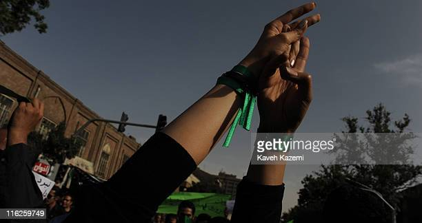 Female demonstrators, supporters of the Green Movement led by Mir Hossein Mousavi, wear green ribbons around their wrists while marching from Imam...