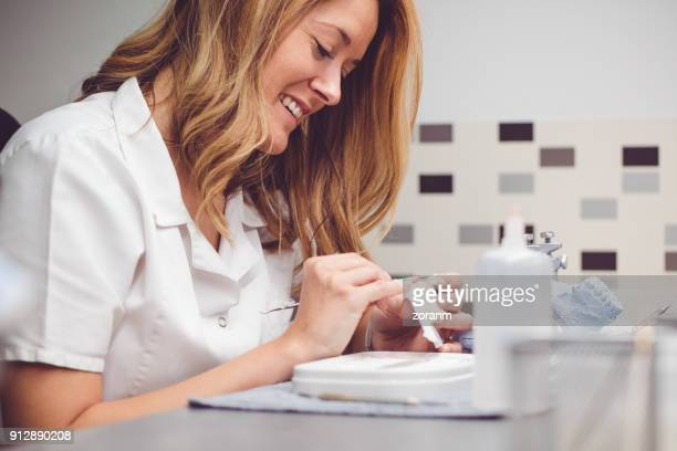 Female dental technician painting prosthetic tooth
