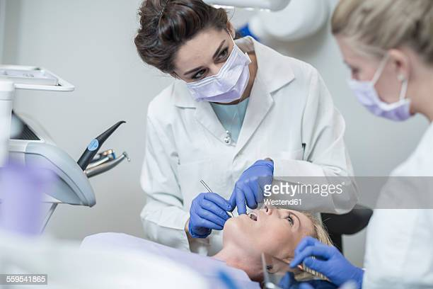 Female dentist examining patient with mouth mirror