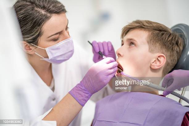 female dentist giving young male patient tooth filling - suction tube stock pictures, royalty-free photos & images