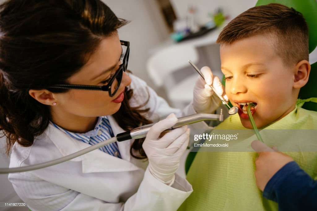 Female dentist giving young male patient tooth filling : Stock Photo