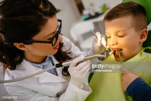Female dentist giving young male patient tooth filling