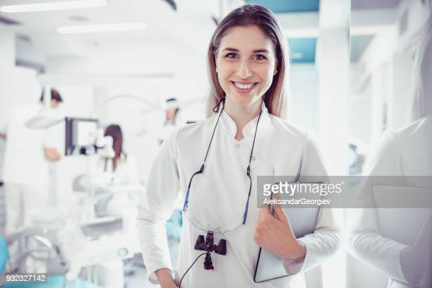 Female Dentist in Dental Clinic with Working Medical Team Behind Her