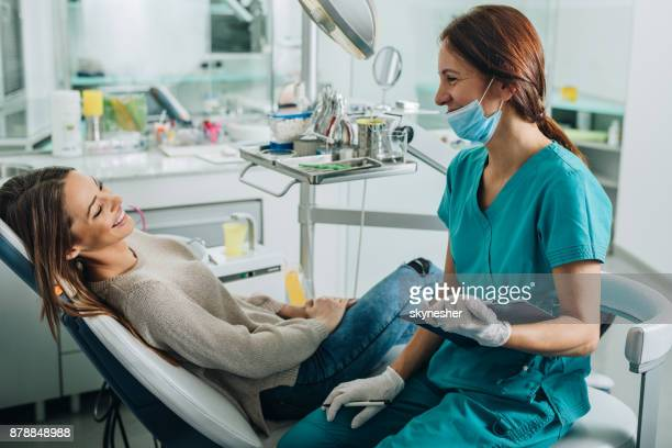 Female dentist talking to her patient at dentist's office.