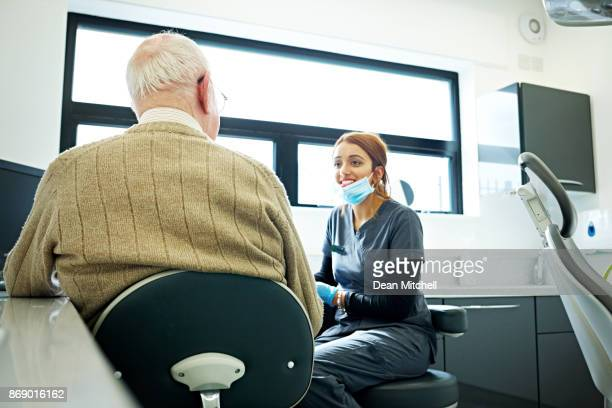 Female dentist talking with senior patient