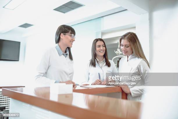 Female Dentists Writing Information About Completed Work For The Day