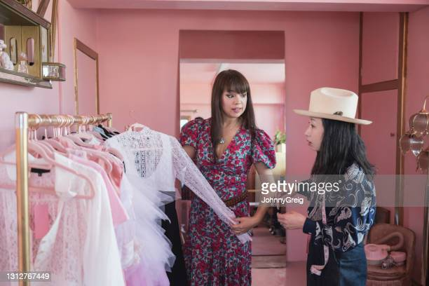 female design partners discussing garment on studio rack - fashion collection stock pictures, royalty-free photos & images