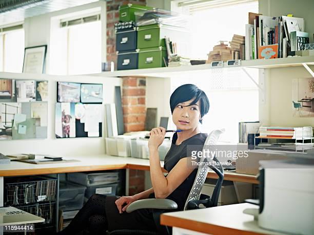 Female designer at desk in office head turned