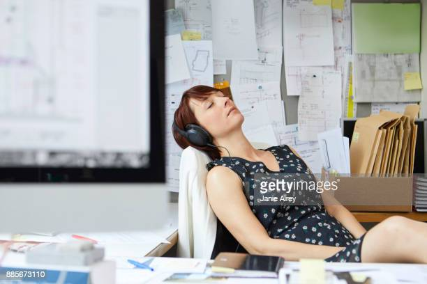 Female designer at office desk listening to headphone music with eyes closed