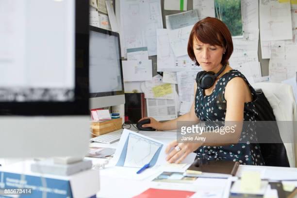 Female designer at office desk looking at blueprint