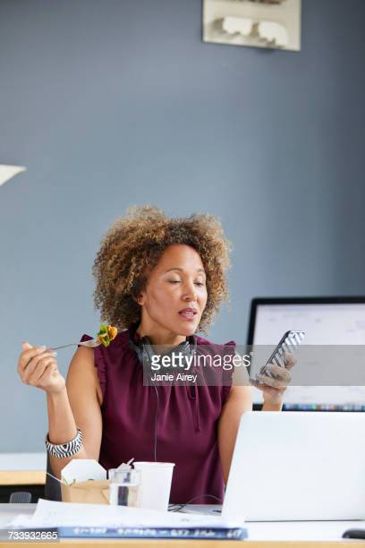 Female designer eating working lunch and looking at smartphone at desk