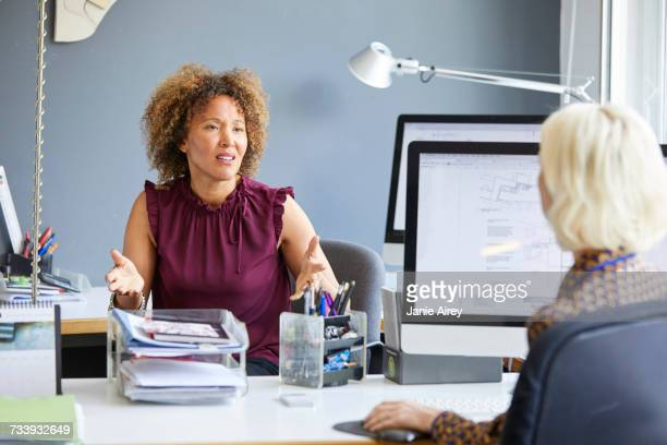 Female designer explaining to colleague in office meeting