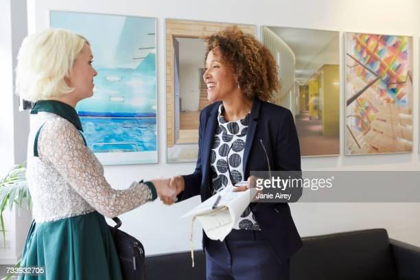 Female designer greeting female client in office lobby