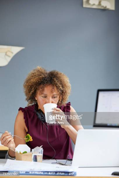 Female designer having working lunch and looking at laptop at desk