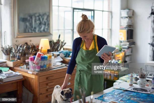 female designer in studio holding digital tablet - pequeño fotografías e imágenes de stock