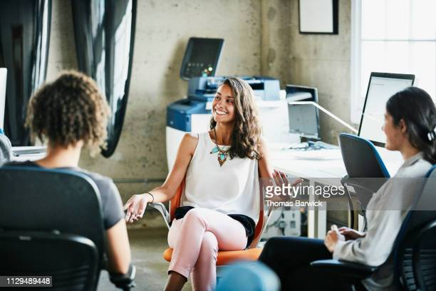female designer leading project meeting with team in office - tenue d'affaires photos et images de collection