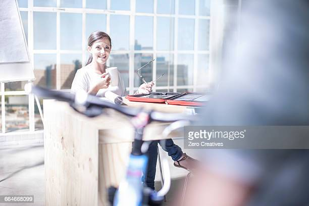 Female designer on design studio patio talking to cycle courier