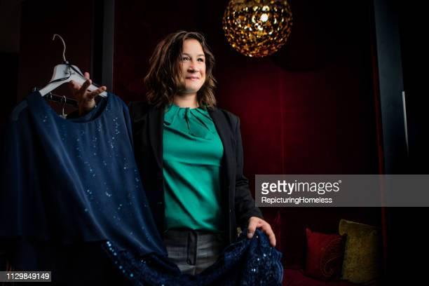Eine Designerin, die das Kleid zeigt, das sie entworfen hat