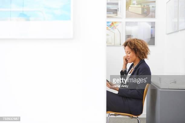 Female designer sitting in office listening to earphones