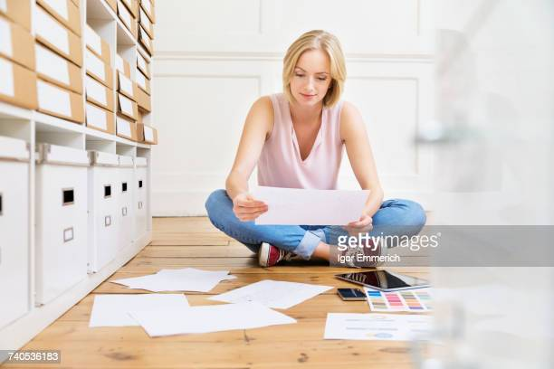 Female designer sitting on floor creating mood board in creative studio