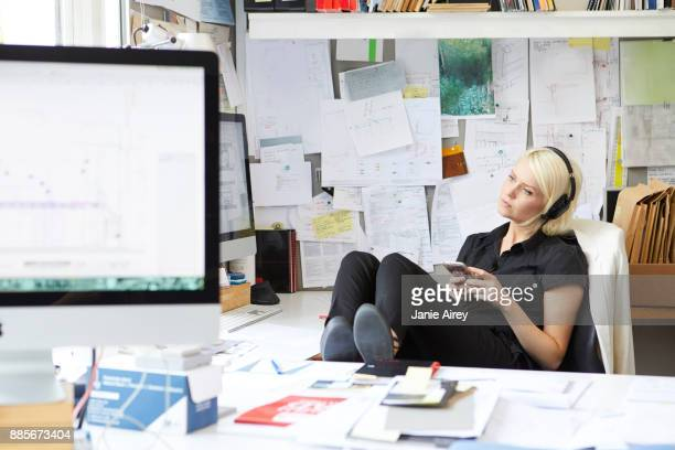 Female designer with feet up at desk listening to headphone music