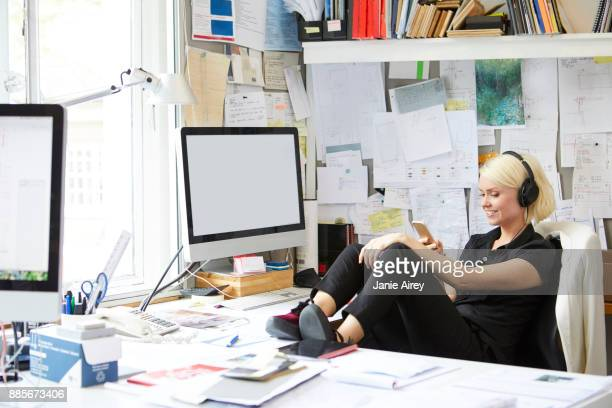 Female designer with feet up at desk looking at smartphone