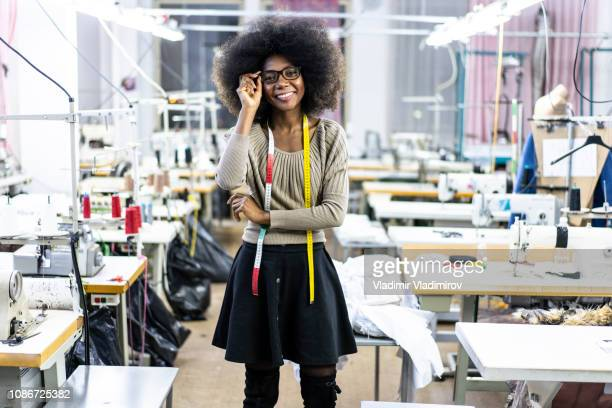 female designer with tape measure in factory - fashion designer stock photos and pictures