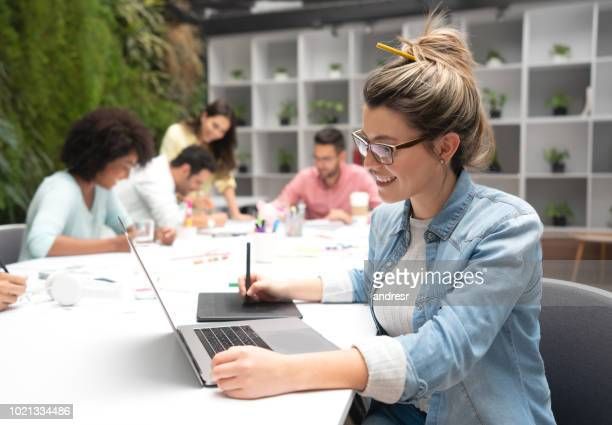 Female designer working at a creative office using a laptop computer