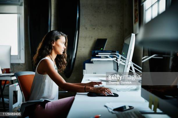 female designer working on computer at workstation in office - small business or entrepreneur stock photos and pictures