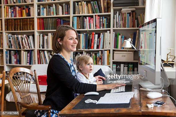 """female designer working with toddler daughter - leanincollection """"working mom"""" stock pictures, royalty-free photos & images"""