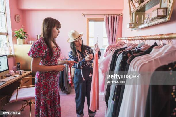 female designers discussing garment from fashion collection - fashion collection stock pictures, royalty-free photos & images